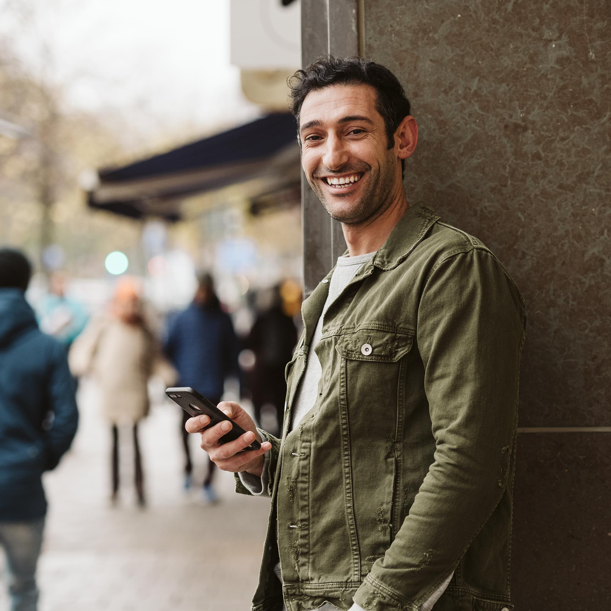Man in the city holding mobile phone.